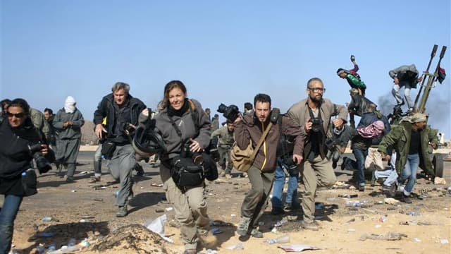 Des journalistes se mettant à couvert lors d'un raid aérien près de Ras Lanouf, en Libye. Au total, 106 journalistes et personnels des médias ont été tués en 2011, contre 94 en 2010. A cela s'ajoute 20 journalistes tués dans des accidents ou des catastrop