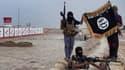 Des combattants de L'EEIL posant avec un drapeau jihadiste à un checkpoint.