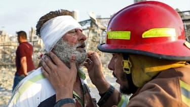 Un pompier portant secours à un homme blessé après les explosions survenues à Beyrouth.