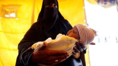 A Sanaa, au Yémen, le 9 juin 2017, une mère tient son fils qui pourrait être atteint du choléra