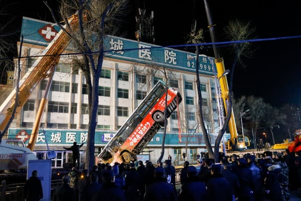 Les équipes de secours chinoises remontent le bus qui a été presque englouti par un trou dans la chaussée, le 13 janvier 2020 à Xining, en Chine