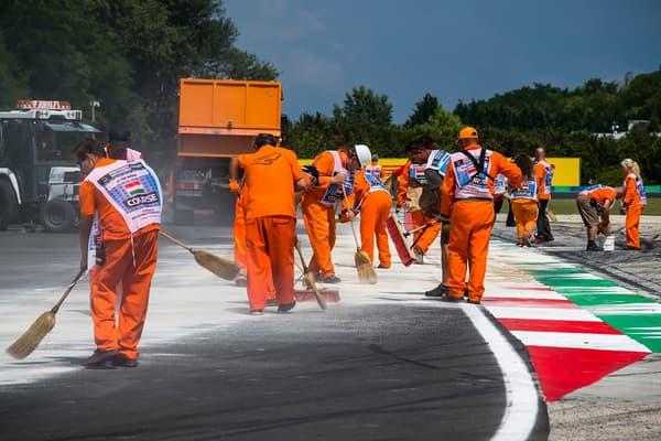 Les commissaires nettoient la piste au GP de Hongrie