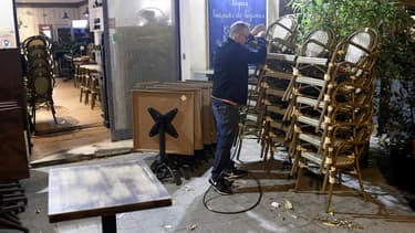Un restaurateur empile son mobilier de terrasse.