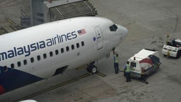 Un avion de la Malaysia Airlines est inspecté sur le tarmac de l'aéroport de Kuala Lumpur, le 13 mars 2014.