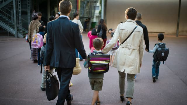 Des parents et leur enfant dans une cour d'école (photo d'illustration)