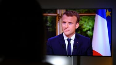 Une femme regarde Emmanuel Macron lors d'un entretien télévisé, à Rennes, le 15 octobre 2017