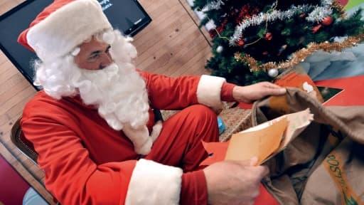 Un employé de la Poste de Libourne déguisé en père Noël ouvre des lettres envoyées du monde entier à l'occasion de Noël, le 8 décembre 2010 dans le centre de tri de Libourne