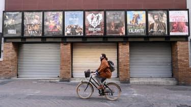 Une femme passant à vélo devant un cinéma fermé de Montpellier en novembre dernier. (Photo d'illustration)