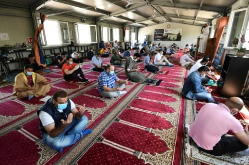 Des musulmans portant des masques et observant les régles de distanciation sociale prient dans une mosquée de Milan, le 5 juin 2020