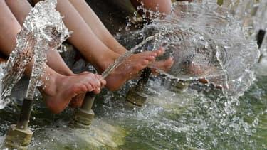 Des touristes se rafraîchissent les pieds dans une fontaine à Montpellier le 2 août, alors que 66 département sont touchés par une vague de canicule.