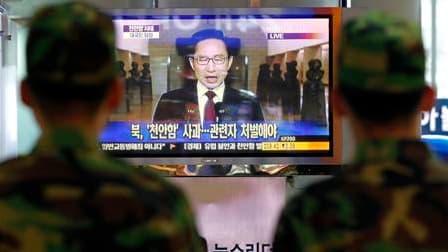 """A la gare de Séoul, des soldats observent la diffusion d'un discours du président sud-coréen Lee Myung-bak. La Corée du Sud a suspendu ses relations commerciales avec son voisin du Nord et a exigé des excuses pour le torpillage de la corvette """"Cheonan"""", q"""