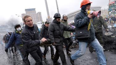 Des opposants évacuent un blessé de la place Maïdan, jeudi 20 février, à Kiev.