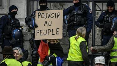 """Une manifestante gilet jaune tient une pancarte """"Pouvoir au peuple"""" à Lyon, le 15 décembre 2018."""