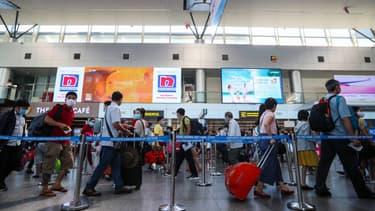 Des passagers masqués font la queue au terminal des départs de l'aéroport international de Danang, à Danang, le 27 juillet 2020.