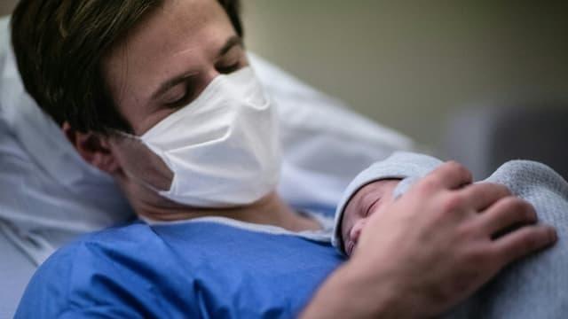 Un père portant un masque tient son bébé contre sa poitrine à la maternité des Diaconesses à Paris, le 17 novembre 2020
