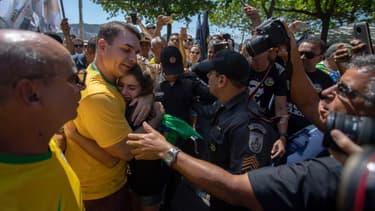 Flavio Bolsonaro, le fils du candidat Jair Bolsonaro, enlace une supportrice de son père lors d'un meeting à Copacabana, à Rio, le 9 septembre.