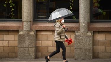 Un femme portant un masque et marchant dans les rues désertes de la ville de Manchester au Royaume-Uni
