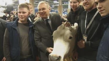 """Jean-Marc Ayrault prend la pause aux côtés d'une vache qui """"bave""""."""
