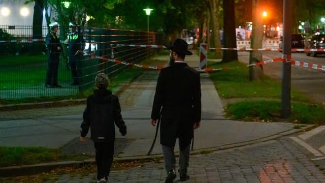 Un homme et un petit garçon devant le lieu de l'agression antisémite, le 4 octobre 2020