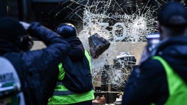 Des manifestants brisent une vitrine, à Paris, le 1er décembre 2018.