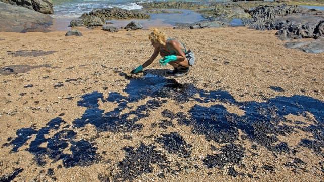 Une bénévole nettoie le pétrole d'une plage à Lauro de Freitas, dans l'Etat de Bahia au Brésil, le 3 novembre 2019