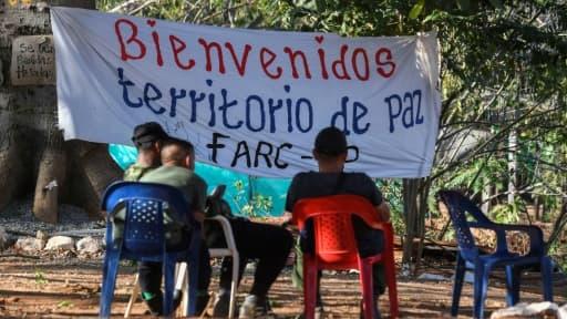 Des membres de la guérilla des Farc assis à l'entrée d'une zone où les rebelles doivent se rassembler pour déposer leurs armes, le 28 février 2017 à San José de Oriente, en Colombie