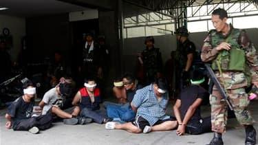 """L'armée thaïlandaise est parvenue mercredi à prendre le contrôle du campement fortifié des """"chemises rouges"""" à Bangkok, forçant les responsables de la contestation à se rendre, mais la capitale et le nord-est du pays restent le théâtre d'émeutes. /Photo p"""