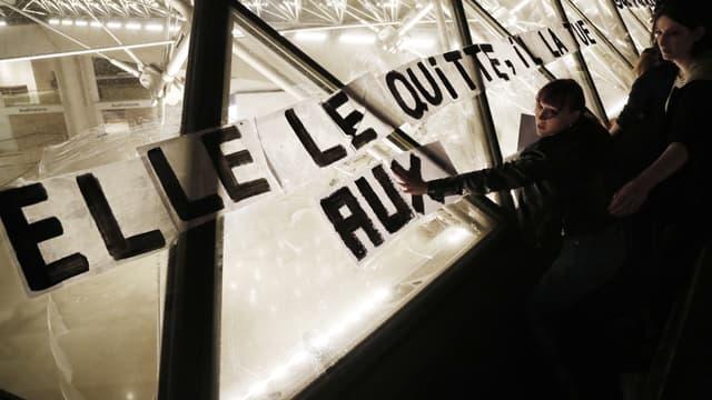 Les colleuses d'affiches placardent des slogans sur la pyramide du Louvre