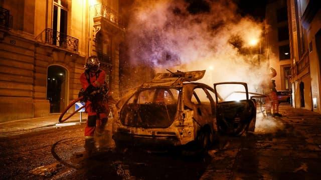 Des pompiers éteigne un feu de voiture dimanche, dans une rue proche des Champs-Élysées