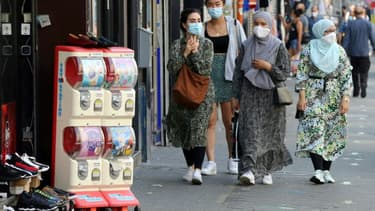 Des femmes portent un masque de protection dans une rue de Bruxelles, le 12 août 2020 en Belgique