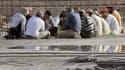 Des travailleurs étrangers d'Arabie saoudite prennent un repas.