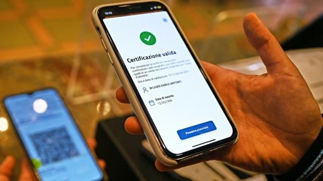 Un gérant de bar vérifie le pass sanitaire d'un client le 6 août 2021 à Rome
