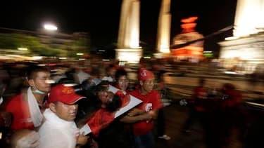 Des opposants au gouvernement thaïlandais transportant un blessé, dans les rues de Bangkok. Après de violents heurts qui ont fait au moins douze morts dans la capitale, l'armée et les manifestants ont appelé au repli, les violences ayant gagné le quartier