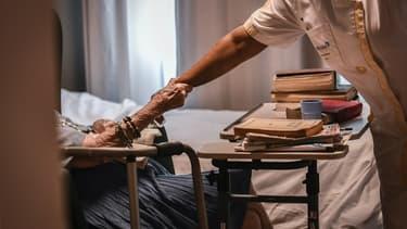 Une personne âgée tenant le bras d'une aide-soignante en juillet 2017, dans un établissement EHPAS parisien.