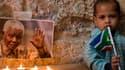 A Jérusalem, un enfant tient un drapeau sud-africain à côté d'un petit autel en hommage à Mandela.