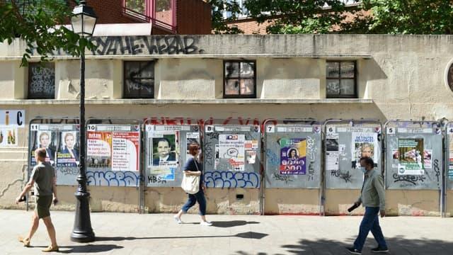 Des passants devant des affiches électorales le jour du 1er tour des régionales, le 20 juin 2021 à Paris