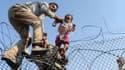 Une photo de Bulent Kilic, photographe de l'AFP primé au Visa pour l'image 2015, montrant un enfant syrien porté au dessus de la frontière.