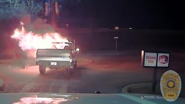 Un pick-up enflammé devant un fast-food écarté par une voiture de police, nous sommes bien aux Etats-Unis.