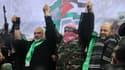 Des leaders du mouvement Hamas: Ismail Haniya (G), porte-parole des Brigades Ezzedine Al-Qassam, Abu Obaida et Moussa Abou Marzouq (D) saluent  les partisans pendant un défilé marquant le 27e anniversaire de la création du mouvement islamiste le 14 Décembre, 2014 dans la ville de Gaza.