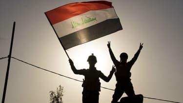 Des soldats de l'armée irakienne qui brandissent le drapeau irakien à Mossoul, le 9 juillet 2017.