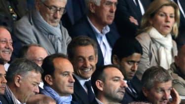 En habitué des lieux, Nicolas Sarkozy est à l'aise dans les tribunes du Parc des Princes, ici entre le président du PSG et celui de Lyon.