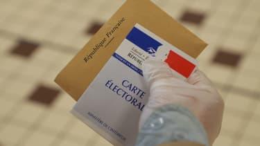 Une main gantée tient une carte électorale le 15 mars 2020, lors du premier tour des élections municipales, à Cucq.