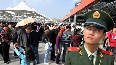 Policier devant les guichets à l'entrée de l'Exposition universelle de Shanghai, qui a ouvert ses portes au public samedi matin. /Photo prise le 1er mai 2010/REUTERS