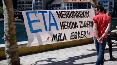 """Un homme passe à côté d'une banderole où est écrit """"ETA avec le peuple, le peuple avec vous. Merci"""", dans le village de Pasajes en Espagne, le 9 avril 2017."""