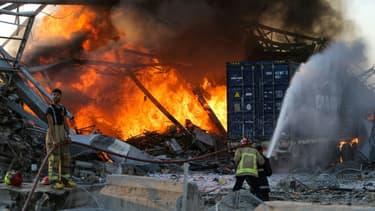 Des pompiers luttent contre un incendie après deux puissantes explosions à Beyrouth, le 4 août 2020