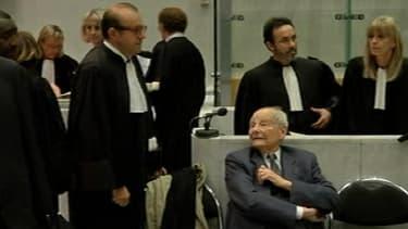 Jacques Servier (d.) entouré de ses avocats, mardi, dans la salle d'audience du tribunal de Nanterre.