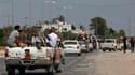 Insurgés libyens faisant route vers Tripoli, la capitale, dont les rebelles disent avoir pris plusieurs quartiers. La France a salué dimanche cette avancée et exhorté Mouammar Kadhafi et ses hommes à déposer les armes. /Photo prise le 21 août 2011/REUTERS