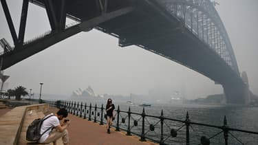 Des touristes avec des masques sous le pont de Harboug Bridge, entouré de la fumée causée par les feux de brousse, à Sydney le 10 décembre 2019