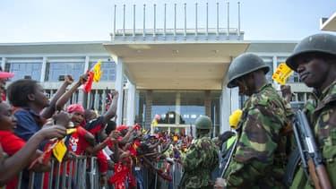 Des partisans d'Uhuru Kenyatta surveillés par l'armée devant le bâtiment où il a donné son discours de victoire, samedi à Nairobi.