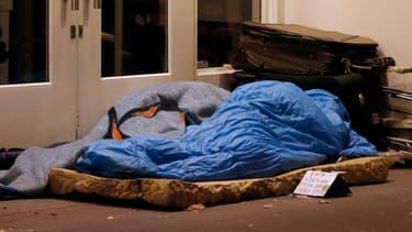 Un SDF se protège du froid dans un sac de couchage, à Paris, en 2012.